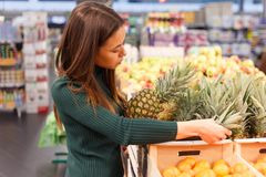 Young brunette woman buying pineapple at grocery shop. royalty free stock photography