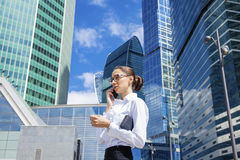 Young brunette woman calling by phone. Beautiful young business woman calling by phone on the background of skyscrapers Royalty Free Stock Images