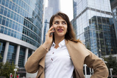 Young brunette woman calling by phone. Beautiful young business woman calling by phone on the background of skyscrapers Royalty Free Stock Photo