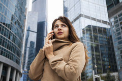 Young brunette woman calling by phone. Beautiful young business woman calling by phone on the background of skyscrapers Stock Photos