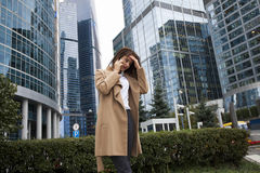 Young brunette woman calling by phone. Beautiful young business woman calling by phone on the background of skyscrapers Stock Image