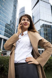 Young brunette woman calling by phone. Beautiful young business woman calling by phone on the background of skyscrapers Royalty Free Stock Image
