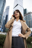 Young brunette woman calling by phone. Beautiful young business woman calling by phone on the background of skyscrapers Royalty Free Stock Photos