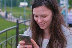 Young brunette woman chatting, typing a message on mobile phone walking along the promenade in the city. Young brunette woman chatting, typing a message on stock image