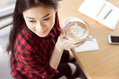 Young brunette woman in checkered shirt holding white cup and drinking cappuccino coffee with decorative bear. High angle view of young brunette woman in Stock Photo