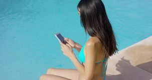 Young brunette woman checking her mobile stock video footage