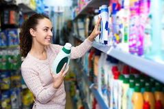 Young brunette woman choosing detergent Royalty Free Stock Photo