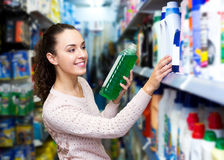 Young brunette woman choosing detergent Royalty Free Stock Image