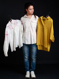 Young brunette woman choosing one  shirt of two Royalty Free Stock Image