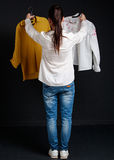 Young brunette woman choosing one  shirt of two Royalty Free Stock Photos