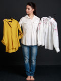 Young brunette woman choosing one  shirt of two Stock Photography