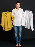 Young brunette woman choosing one  shirt of two Royalty Free Stock Photography