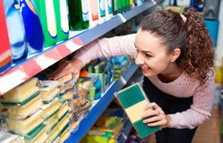 Young brunette woman choosing sponges in household section Stock Image