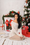 Young brunette woman in christmas interior Stock Photos
