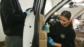 Young brunette woman and young man clean car interior in the service station