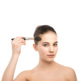 Young brunette woman with clean face. Girl perfect skin applying cosmetic brush. Isolated on a white. Stock Photography