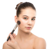 Young brunette woman with clean face. Girl perfect skin applying cosmetic brush. Isolated on a white. Royalty Free Stock Photography