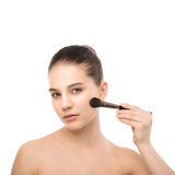 Young brunette woman with clean face. Girl perfect skin applying cosmetic brush. Isolated on a white. Royalty Free Stock Image