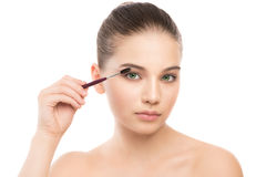 Young brunette woman with clean face. Girl perfect skin applying cosmetic brush. Isolated on white. Stock Photography
