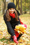 A young brunette woman collecting fallen leaves Stock Photos