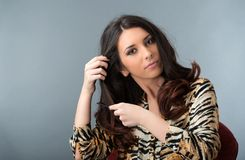 Brunette woman combing her hair Royalty Free Stock Images