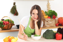 Young brunette woman is cooking or eating fresh salad in the kitchen. Housewife holding wooden spoon in her right hand Royalty Free Stock Photo