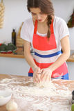 Young brunette woman cooking pizza or handmade pasta in the kitchen. Housewife preparing dough on wooden table Royalty Free Stock Images