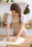 Young brunette woman cooking pizza or handmade pasta in the kitchen. Housewife preparing dough on wooden table Stock Photos