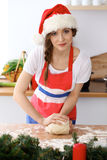 Young brunette woman cooking pizza or handmade pasta while wearing Santa Claus cap  in the kitchen. Housewife preparin Stock Photography