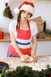 Young brunette woman cooking pizza or handmade pasta while wearing Santa Claus cap  in the kitchen. Housewife preparin Stock Photo