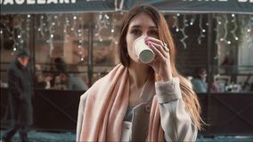 Young brunette woman with cup of coffee standing in front of show-window. Girl dreaming to buys clothes. Slow motion. stock footage