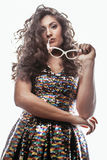 Young brunette woman with curly hairstyle in fancy glamur dress isolated on white background gesturing emotional. Close up Royalty Free Stock Image