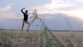 Young brunette woman dance rhythmic gymnastics, modern with red ribbon. stock video footage