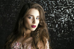 Young brunette woman on dark studio wall background Stock Photo