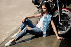 Young brunette woman in denim vest sitting near motorcycle and looking away Royalty Free Stock Photography