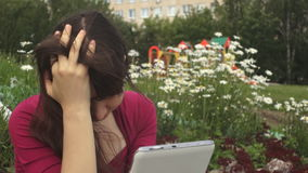 Young brunette woman in depression using a tablet next to daisies in the park. Young brunette woman in depression using a tablet while holding her head in her stock video