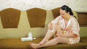 Young brunette woman doing depilation of the legs with wax and a napkin at home. Overall plan stock footage