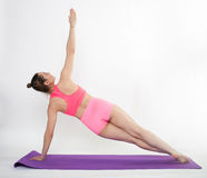 Young brunette woman doing pilates exercises on mat isolated Royalty Free Stock Images