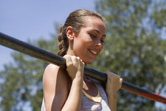 Young  brunette woman doing pull-up on a sports horizontal bar a Stock Photo