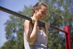 Young brunette woman doing pull-up on a sports horizontal bar a. T summer day in park stock photos