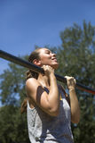 Young  brunette woman doing pull-up on a sports horizontal bar a. T summer day in park Royalty Free Stock Photography