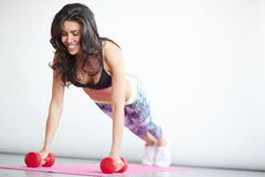 Young brunette woman doing push-up in gym Royalty Free Stock Image