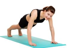 Young brunette woman doing push ups royalty free stock photography