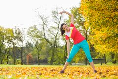 Young brunette woman doing yoga exercises. Young brunette woman doing yoga exercises in a autumn park Stock Photo