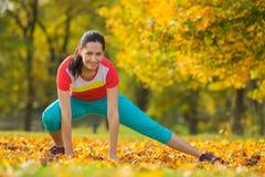 Young brunette woman doing yoga exercises. Young brunette woman doing yoga exercises in a autumn park Stock Photos