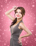 Young brunette woman in a dress on a snowy background. Beautiful brunette with luxury golden necklace over pink winter background. Christmas concept Stock Image