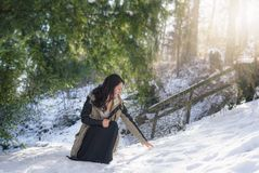 Beautiful woman reaching for snow. Young brunette woman, dressed in a winter jacket and black skirt, in a squat position, reaching for snow, on a sunny day, in stock images