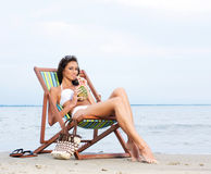 A young brunette woman drinking a cocktail and relaxing on the beach. A young and attractive brunette Caucasian woman in a white swimsuit drinking a cocktail and Stock Image