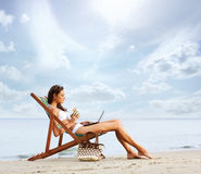 A young brunette woman drinking a cocktail and relaxing on the beach Stock Photos