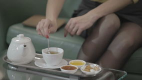Young brunette woman drinks a tea on the green sofa in a hotel. Camera moves from down to up. Young brunette woman sitting in the hall of hotel and pours the tea stock video